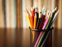 Wire desk tidy full of coloured pencils